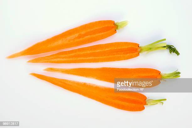 Four slices of carrot with top on white background, close-up