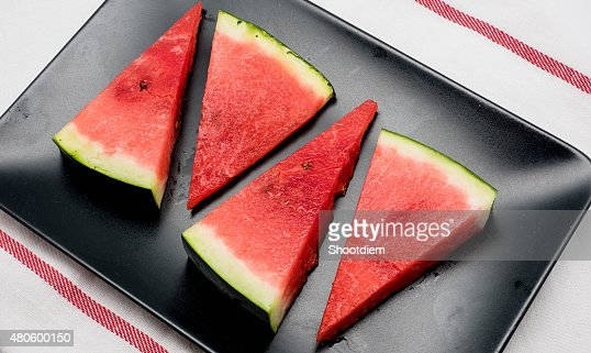 Four slices of watermelon on black dish : Stock Photo