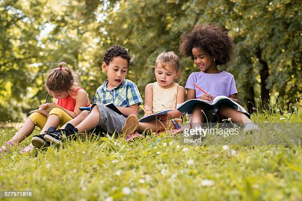 Four small friends relaxing in nature and writing in notebooks.
