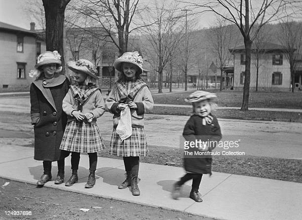 Four smartly dressed young girls wearing flower decorated straw bonnets two wearing tartan outfits standing on an urban American street pavement with...