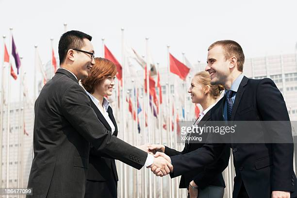 Four smiling business people meeting and shaking hands outdoors, Beijing