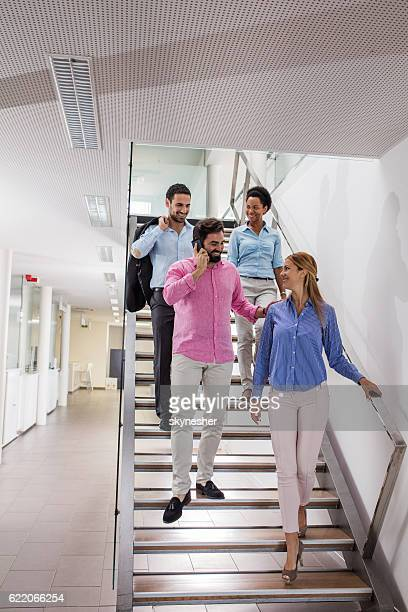 Four smiling business people walking down the stairs.