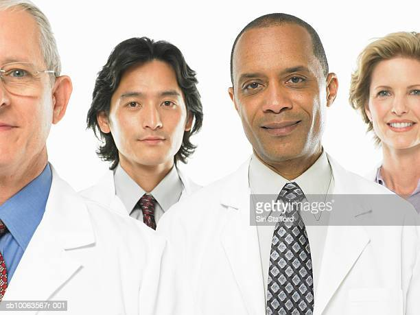 Four smiling doctors on white background, portrait