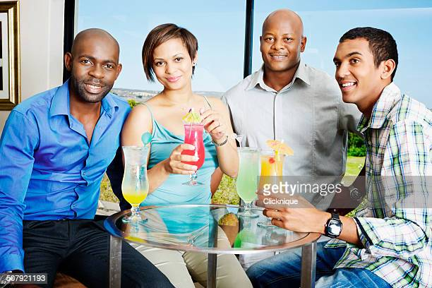 Four smiling yound adults drinking cocktails in bar lounge