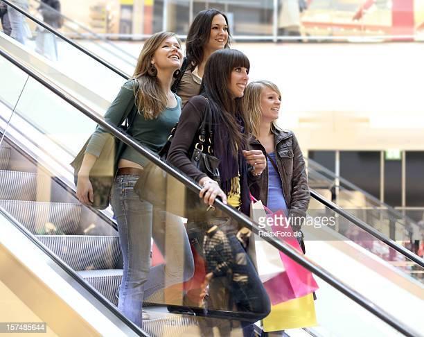 Quatre souriant jeune femme avec multicolore sur l'escalator des sacs