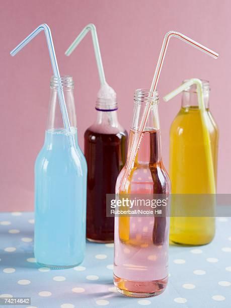Four soda bottles with straws