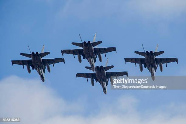 Four Spanish Air Force F-18M Hornets fly in formation above Spain.