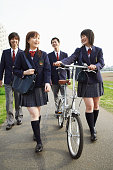 Four Students in Uniform Walking Outdoors, One Holding a Bicycle