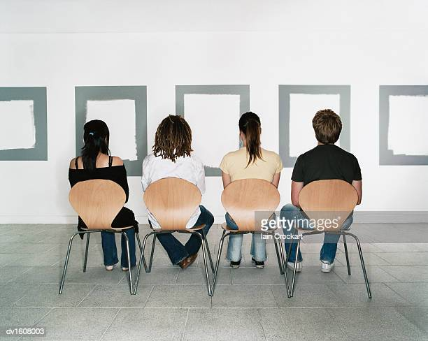 Four Students Sit and Contemplate Five Empty Frames