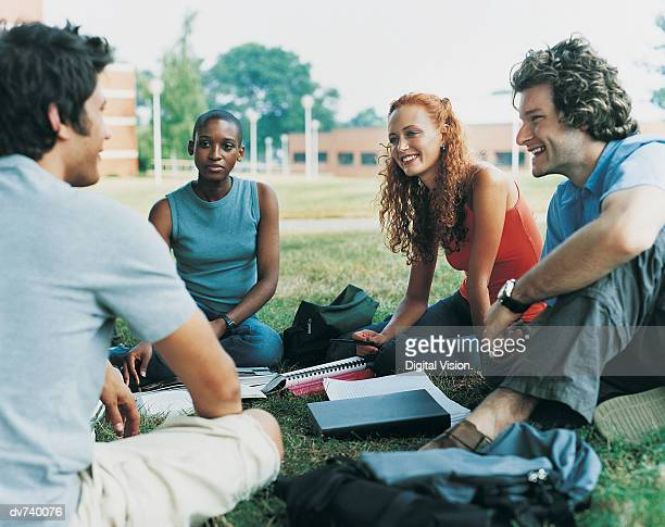 Four Students Sitting Outdoors on Campus