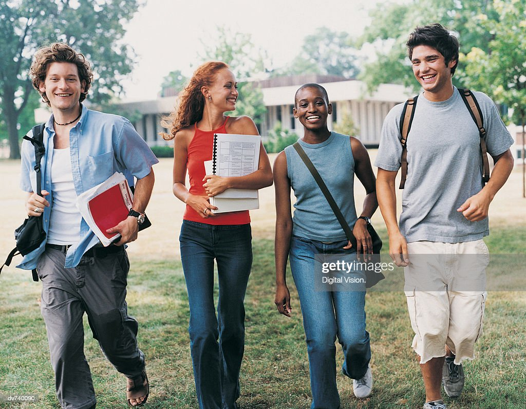 Four Students Walking on Campus : Stock Photo