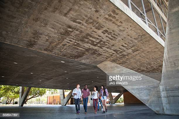 Four students walking underneath building