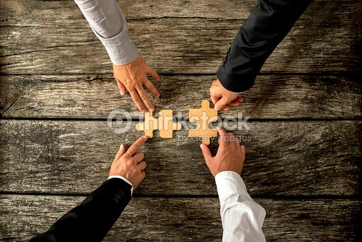 Four successful business men joining two puzzle pieces each bein