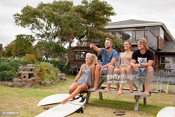 Four surfer friends sitting on picnic bench