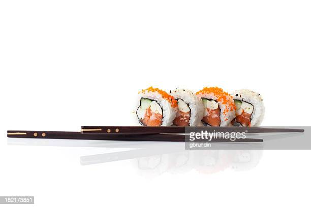 Four sushi rolls with two black chopsticks