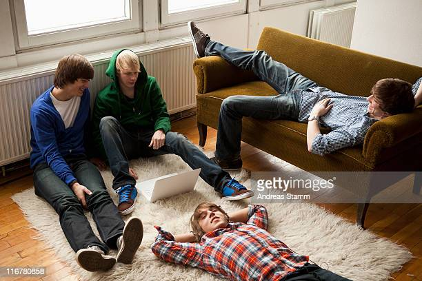 Four teenage friends hanging out in a living room