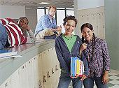 Four teenage girls and boys (15-17) in locker area, portrait