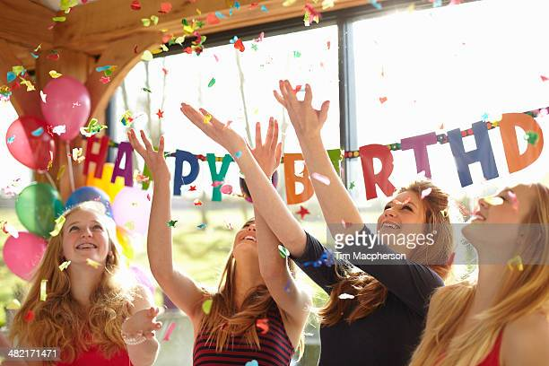 Four teenage girls celebrating with confetti at birthday party
