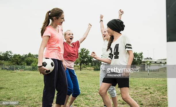 Four teenage girls having fun on a soccer field