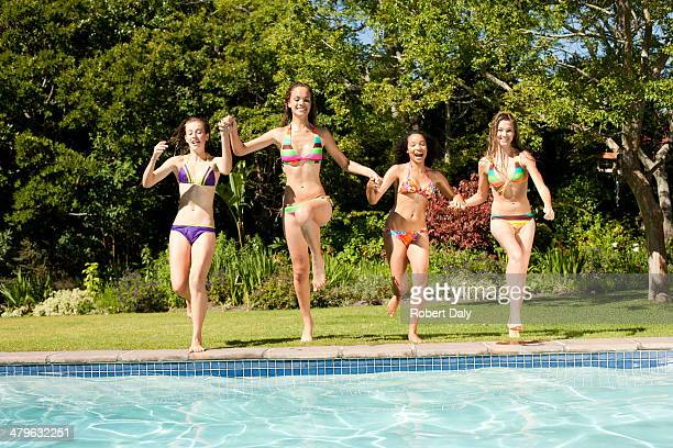 Four teenage girls jumping into pool