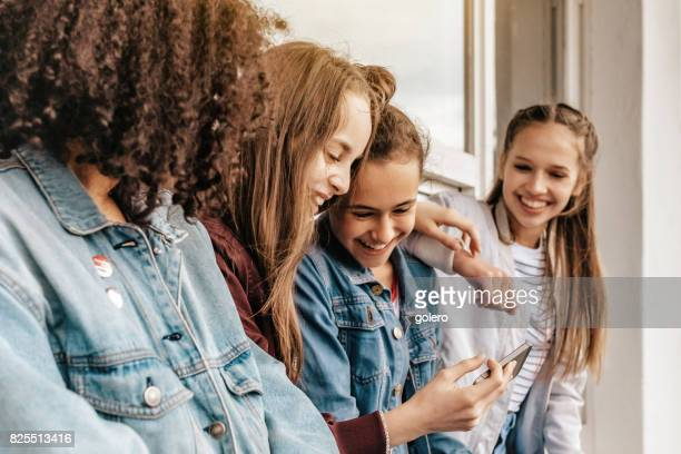 four teenage girls looking together at smartphone