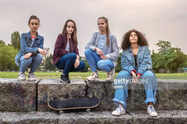 four teenage girls on stairs in park