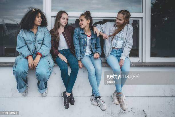 four teenage girls sitting on window outdoors