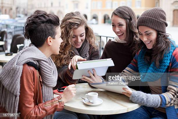 four teenage girls studying together at a café