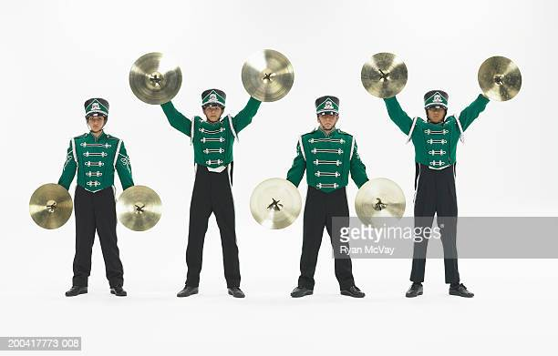 Four teenagers (14-18) in band uniforms holding cymbals, portrait