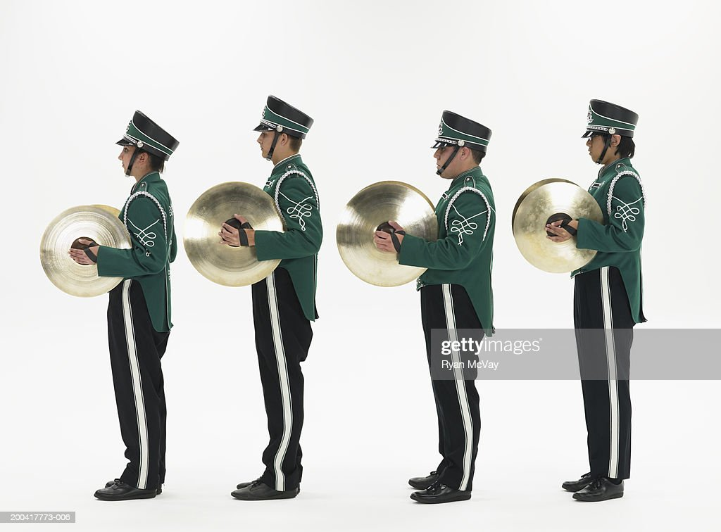 Four teenagers (14-18) in band uniforms holding cymbals, side view : Stock Photo