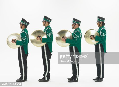 Four teenagers (14-18) in band uniforms holding cymbals, side view