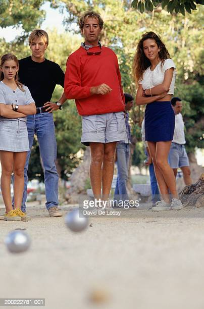 Four teenagers (16-17) playing bocce ball, ground view