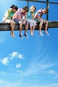 Four teenagers sitting on wooden bridge against blue sky