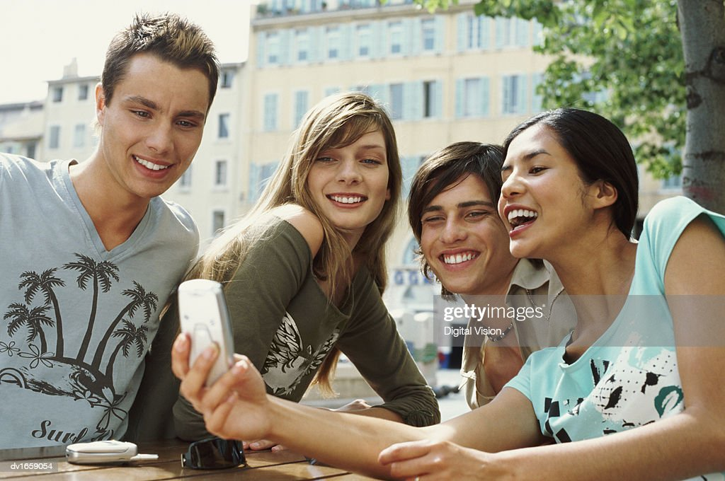 Four Teens Sitting at a Table and Using a Videophone : Stock Photo