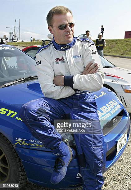 Four times world rally champion Tommi Makinen of Finland relaxes on his Subaru Impreza before driving the '0' car one of course safety cars on the...