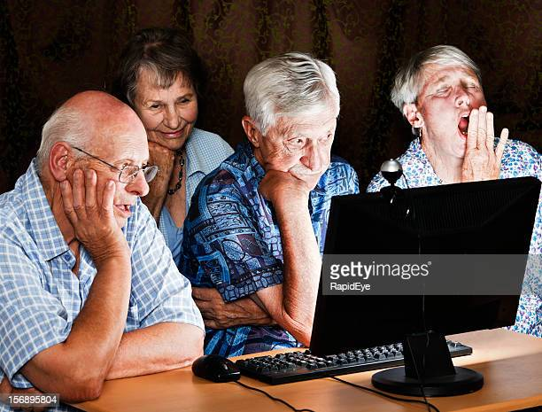 Four tired, bored seniors sit round a computer at night