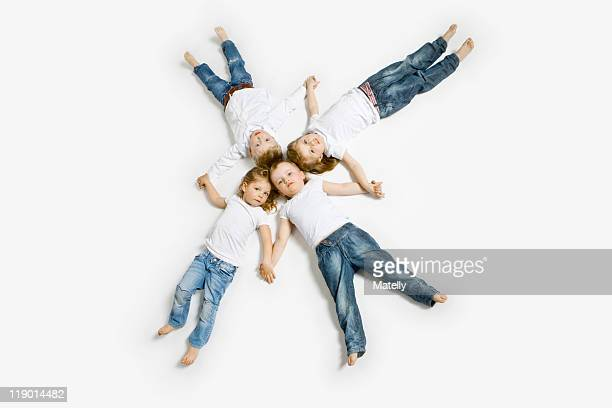 Four toddlers laying in formation