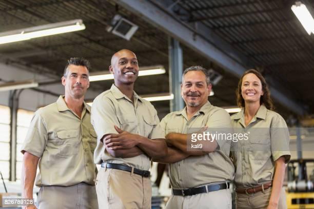 Quatre travailleurs de l'entreprise dans le garage de camionnage