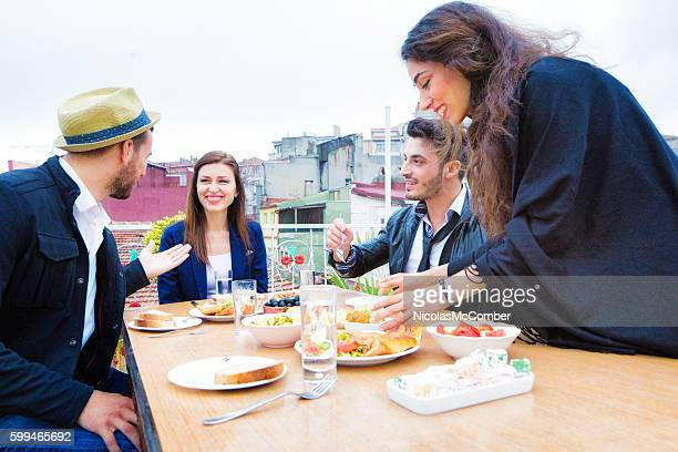 Four Turkish friends meeting for lunch on Istanbul rooftop