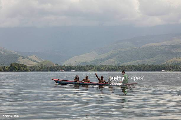 Four villagers from Asei in a canoe with outboard motor on Lake Sentani a shallow lake of some 104 sq km with three unique fish species and no fewer...