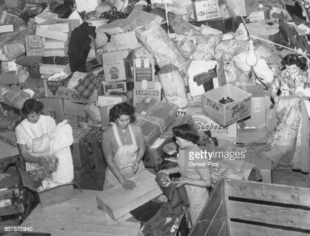 Four volunteer women begin sorting approximately 35 tons of clothing shoes and bedding donated for Korean and European relief in a Sunday collection...