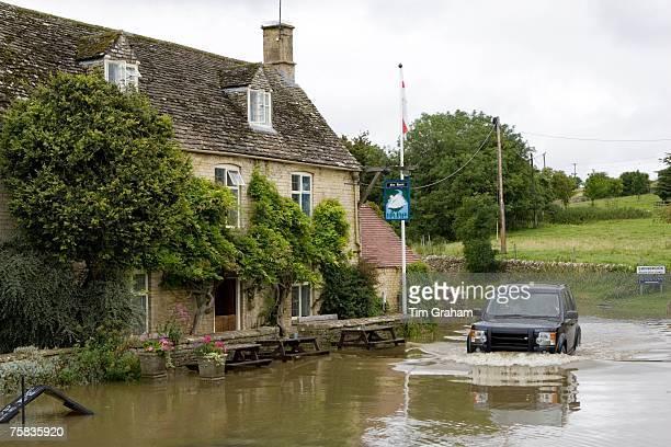 Four wheel drive car drives through flooded road in Swinbrook Oxfordshire England United Kingdom