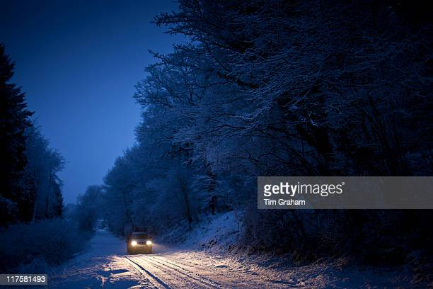 Four wheel drive car in traditional snow scene in The Cotswolds Swinbrook Oxfordshire United Kingdom
