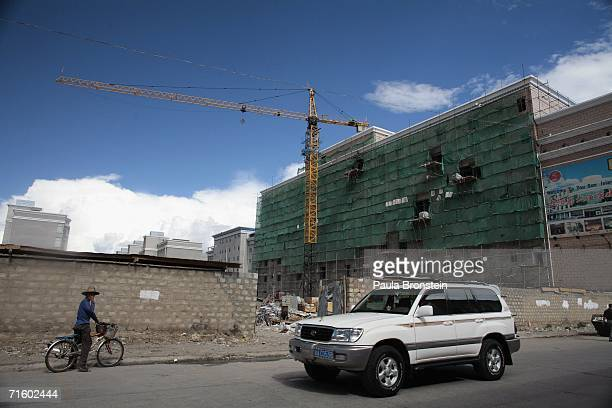 A four wheel drive car passes by a construction site for a new hotel in the new part of Lhasa city on August 6 2006 in Lhasa of Tibet Autonomous...