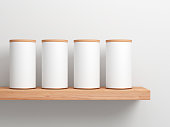 Four White Tin Can Mockup on wooden shelf. Cylindrical packaging, 3d rendering