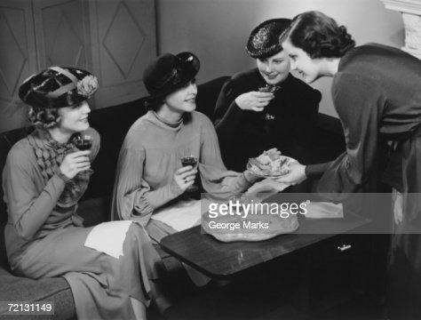 Four women drinking wine, talking in living room (B&W)