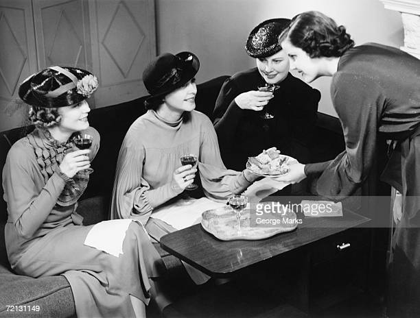 Four women drinking wine, talking in living room (B&W)