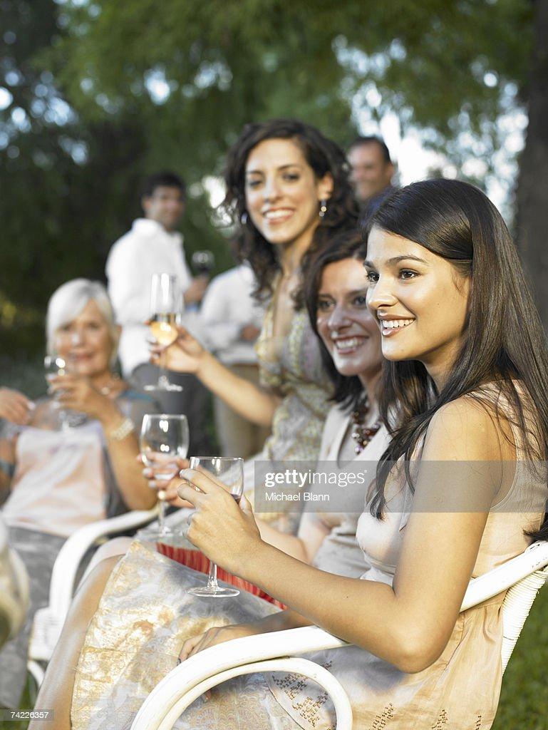 'Four women relaxing in garden, drinking wine' : Stock Photo