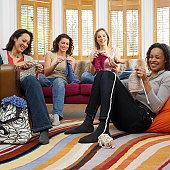 Four women relaxing in lounge, knitting, smiling