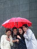 Four women sharing umbrella in rain, laughing